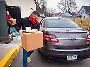 "06 APRIL 2020 - DES MOINES, IOWA: Executive Pastor JEFF OSTRANDER brings a box of food to a family in a car during a drive through emergency food distribution at First DSM Church in Des Moines. Volunteers brought food to the people in the cars to maintain proper ""social distancing."" On Monday, 06 April, Iowa reported 946 confirmed cases of the Novel Coronavirus (SARS-CoV-2) and COVID-19. There have been 25 deaths attributed to COVID-19 in Iowa. Most non-essential businesses are closed until 30 April. Well over 100,000 Iowans filed first time claims for unemployment in the last three weeks, more than applied during the peak of the Great Recession of 2008. Local food banks have seen an equal spike in people seeking nutritional assistance. First DSM Church has increased their food pantry from one day weekly to three days per week. Hundreds of people lined up Monday to get a box of food and one roll of toilet paper at the church's drive through pantry.          PHOTO BY JACK KURTZ"