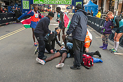 NYRR New York City Half Marathon: Mo Farah on ground after collapse after finish of race, receives medical attention as race director Mary Wittenberg attends, other top finishers Mutai, Sambu lookon, Matt Tegankamp holds Farah's daughter to the side,