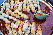 "03 OCTOBER 2012 - BANGKOK, THAILAND:      Grilled fishballs in spicy sauce at a snack stand in Khlong Toey Market in Bangkok. Khlong Toey (also called Khlong Toei) Market is one of the largest ""wet markets"" in Thailand. Thousands of people shop in the sprawling market for fresh fruits and vegetables as well meat, fish and poultry every day.     PHOTO BY JACK KURTZ"