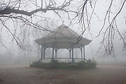 London park bandstand on an early misty morning. Ruskin Park is situated in Denmark Hill, Lambeth, London, England. The park was designed by Lt Col J. J. Sexby (who also designed Battersea, Ruskin and parts of Southwark Parks). It was opened on 2 February 1907 with an area of 24 acres and in 1910 a further 12 acres were added on the south side of the park. It is named after John Ruskin (1819 – 1900), who lived near to the park. Nowadays, the park is used by families and dog walkers, the bandstand used during warmer months for summer concerts and music events.