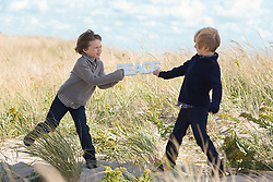two boys fighting over the word peace on the beach in The Hamptons