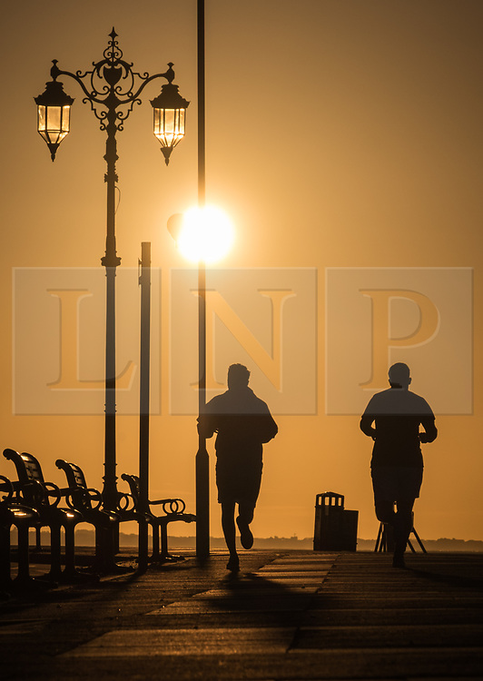 © Licensed to London News Pictures. 12/09/2017. Southsea, UK.  The silhouette of a two men jogging along Southsea Promenade shortly after sunrise this morning, 12th September 2017. Photo credit: Rob Arnold/LNP
