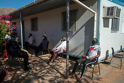 Pregnant women waiting to be seen at De Doorns Clinic, a Western Cape government facility, in the Cape Winelands, where social-distancing rules are in effect, Wednesday May 6, 2020. The COVID-19 pandemic is a challenge, explains Abrey Arendse, Operational Manager here. Each morning, hundreds of patients line up outside the fenced clinic, according to social-distancing markers on the ground. She personally assesses everyone to see who needs to come inside the clinic right away, including the elderly, very sick, pregnant ladies and disabled people. Due to COVID-19, and space reasons, she can't let them all inside. There is also not enough PPE on hand for patients and no long-term stock for staff. Meanwhile, it's difficult to leave patients waiting in the elements outside. The sun is strong, and the winter rains are coming. PHOTO: EVA-LOTTA JANSSON