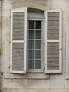 window with hakf open shutters France