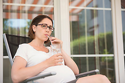 Drinking water relaxing terrace pregnant woman