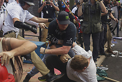 August 12, 2017 - Charlottesville, Virginia, United States - A White Supremacist beats a man into the ground in a brawl at Lee Park on 12 August 2017 in Charlottesville, Virginia, USA.  The Unite the Right instigated brawls between Antifa and various leftists. The brwal ensued and the White Supremacists/Alt Right supporters were forcibly removed by police. (Credit Image: © Shay Horse/NurPhoto via ZUMA Press)