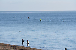 © Licensed to London News Pictures. 10/01/2021. Brighton, UK. Paddle boarders take to the sea at Brighton on the south coast during the third national lockdown. Photo credit: Liz Pearce/LNP