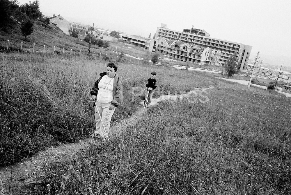 Two friends navigate their way to school past a probable minefield, Sarajevo.The Blind School Sarajevo, is the only centre in Bosnia for children and young adults. It was extensively damaged during the civil war an was used by the Bosnian Serb army as a military position from which to snipe and shell the city. The few teaching staff left during the war managed to visit some of their blind pupils and continue a limited education. The school reopened after the war ended but conditions remain dire.
