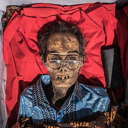 Todeng died in 2009. He has been burried with his purse and favorite glasses<br /> <br /> The Ma'Nene Ritual is about to start. The coffins have been dragged out of the family's mausoleum. After cleaning the dead body, clothes will be changed before having a sunbath. Rising to Puya (Heaven) also means to enter the afterlife. And, to continue with the living standards one is used to when being on earth. That's why it is customary for the Torajans to put a gift in the coffin of their ancestors before locking it into a family mausoleum or the traditional stone grave. For some, a bracelet or a watch would do, while the highest cast might even bury a diamond with their loved ones. Nowadays, many are afraid their gifts get stolen. Local police authorities are even investigating cases of stolen mummies. The rumor spread that there's a high demand from foreign antique-collectors based in Bali. Supposedly, they're hiring thieves from the area to steel bodies for their private exhibitions. Not to forget about the missing baby mummies who apparently are used for occult medicine.