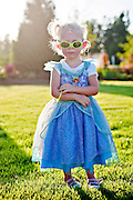 A young child dressed in costume stands in a field as the sun sets..