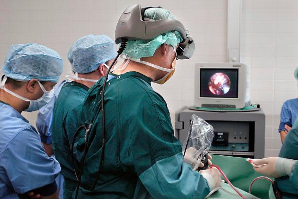 Nederland, Nijmegen, 30-4-2005Chirurg voert operatie uit d.m.v. endoscoop, kijkbuis, aan de hypofyse, waar zich een tumor, kankergezwel bevindt.Via een speciale helm wordt het videobeeld direct voor zijn ogen geprojecteerd. De buis wordt eerst door een kno chirurg via de neus ingebracht. moderne operatietechniek, medische techniek, vooruitgang chirurgie, hersenchirurg, hersenoperatie, hersentumor, gezondheidszorg, academisch ziekenhuis umc Radboud,Foto: Flip Franssen