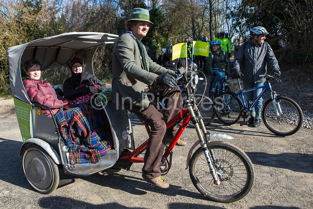 A male rickshaw driver and two female passengers wait for the opening of the restored Devonshire Tunnel as part of the Two Tunnels Greenway in Bath, Somerset, England, United Kingdom on 6th April 2013.  The rickshaw displays two Sustrans flags.  Sustrans is a charity that works with communities, policy-makers and partner organisations so that people can choose healthier, cleaner and cheaper journeys and enjoy better, safer spaces to live in.  The restoration The restoration of the tunnels and 13-mile path has been organised by Sustrans, working in partnership with Bath and North East Somerset Council.   The event was attended by hundreds of cyclists and pedestrians of all ages and abilities.