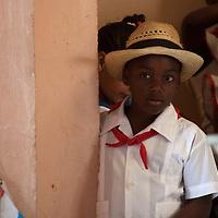 Central America, Cuba, Santa Clara. Shy Cuban Boy in Hat.
