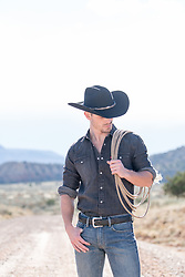 cowboy holding a lasso on a dirt road overlooking mountains