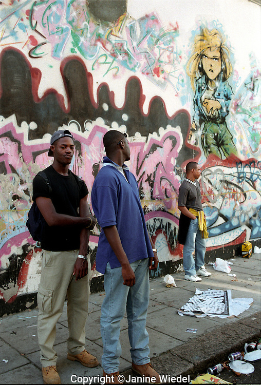 Youth hanging around in front of a mural in the back streets of Notting Hill Gate London.
