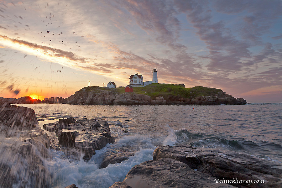 Waves crash on rocky shoreline at Nubble aka Cape Neddick Lighthouse in York, Maine, USA
