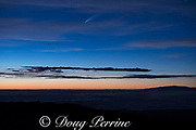 Comet C/2020 F3, aka comet Neowise, is visible from the slopes of Mauna Loa after sunset, with the peak of Maui's Haleakala volcano visible below on right, Hawaii, United States ( Central Pacific Ocean )