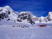 Two of K2 Aviation's Cessna 185s on wheel skis at the Southeast Fork of the Kahiltna Glacier Base Camp, Mount Hunter beyond, Denali National Park, Alaska.
