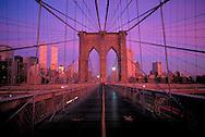 Brooklyn Bridge; New York City, NY, designed by John Augustus Roebling, on bridge looking at Manhattan, Dusk