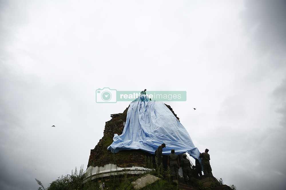 August 1, 2018 - Kathmandu, Nepal - Firefighters use tarpaulin to preserve the Dharahara from rain and other further damages on the initiation of the Deputy Mayor, Hari Prabha Khadki in Kathmandu, Nepal on Wednesday, August 01, 2018. The Dharahara was once a nine-storey tower that collapsed during the earthquake in 2015. (Credit Image: © Skanda Gautam via ZUMA Wire)
