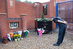 © Licensed to London News Pictures . 18/09/2013 . Hyde , UK . A policeman reads tributes . Flowers and tributes in memory of PCs Fiona Bone and Nicola Hughes at a memorial garden at Hyde police station this morning (18th September 2013) . The two PCs were on duty one year ago today (18th September 2012) , when they were murdered by Dale Cregan , whilst responding to a fake 999 call that he'd placed . A private family memorial event is due to take place at the gardens later this morning (18th September 2013) at 10:53 , at the time to two were murdered . Photo credit : Joel Goodman/LNP