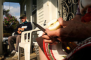 Carl Adams sits on the porch after planting 30 of a planned 200 bulbs for spring flowers as Pat Adams cuts up MacIntosh apples from a tree in her Lebanon, N.H. yard to freeze for winter pies Friday, September 30, 2011. <br /> Valley News - James M. Patterson