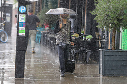 © Licensed to London News Pictures. 28/07/2021. London, UK. A woman shelters under an umbrella during a torrential downpour in north London. According to The Met Office, wet weather is expected in the capital for this week. Photo credit: Dinendra Haria/LNP