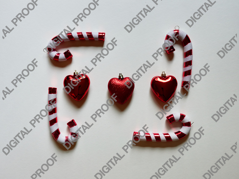 Christmas candy cane and hearts at studio above view over a white background isolated flatlay