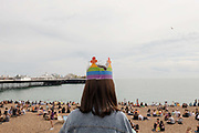 A woman with dark hair wearing a rainbow coloured paper crown after the Brighton Pride parade on the 3rd August 2019 in Brighton in the United Kingdom.