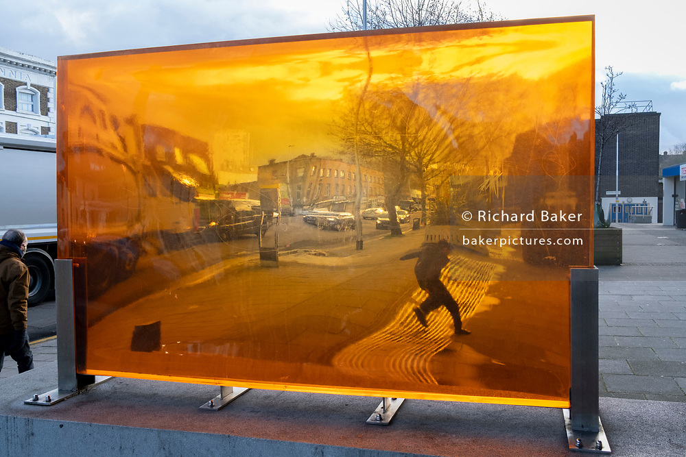 Seen through an orange-coloured prism, a figure leaps over the lines of the pavement on a south London street, its distorted perspective and geometry caused by the convex and concave shape of its thick lens, on 29th January 2021, in London, England.