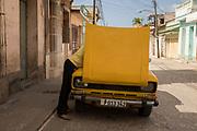 A man takes care of his vintage car in Trinidad, Cuba.
