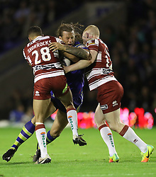 Warrington Wolves' Ashton Sims is tackled by Wigan Warriors Jake Shorrocks (left) and Wigan Warriors Liam Farrell (right), during the Super 8's match at the Halliwell Jones Stadium, Warrington.
