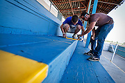 Luke Miller and Stephen Larson, working with the North Idaho Fair, stencil in seat dividing lines at the Kootenai County Fairgrounds Grandstand on Wednesday afternoon.