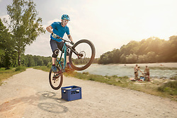 Man jumping with mountainbike over beer crate, Bavaria, Germany