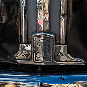 The city of Havana reflected in the chrome of a vintage car.