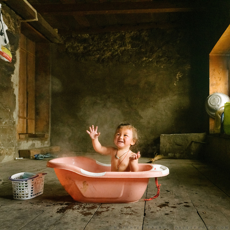 A baby girl is getting a bath with heated water during a snow storm. Inside a traditional Layap home.