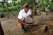 Ecuador, May 8 2010: Martin uses a machete to shape a small spear at the Huaorani EcoLodge. Copyright 2010 Peter Horrell