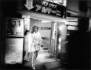 """Hostesses from """"Armani"""" climb up to street in heart of Kabuki-cho Red Light District, Tokyo, Japan.  Hostesses, """"if they want to make real money"""", are encouraged to go home with clients at the end of the evening."""