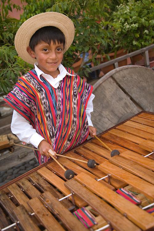 Central America, Guatemala, Antigua, boy in traditional clothing playing marimba