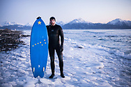 Kyle Kornelis stops for a photo on after a mid winter twilight surf session in Alaska.