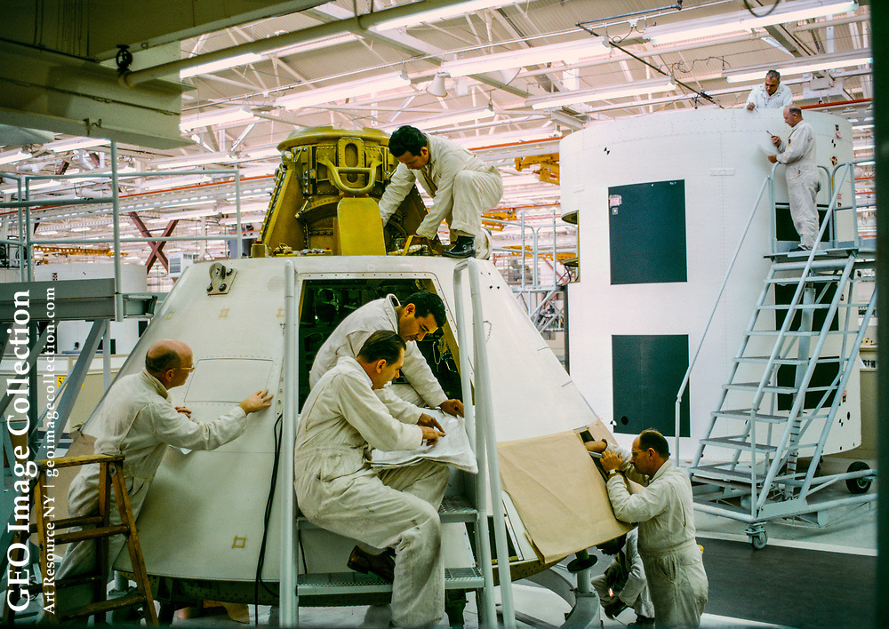 Technicians at the North American Rockwell Corp. work on an Apollo command module.