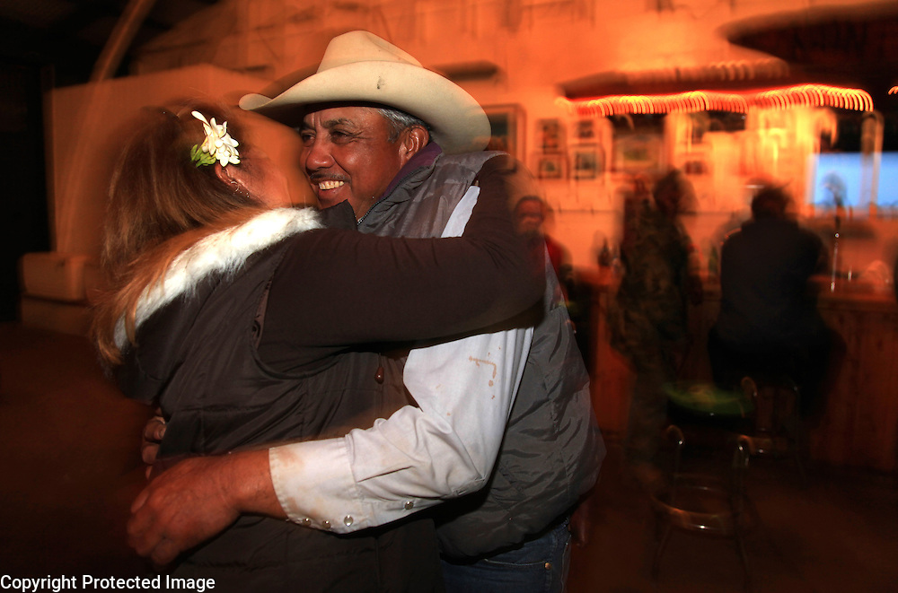 """Godfrey Kainoa, one of the few known descendents of the original Mexican """"vaqueros"""" who taught the Hawaiians their cowboys skills, dances with his girlfriend, Johnelle """"Amoo"""" Ching in the Kahua Ranch barn in North Kohala, Hawaii--which sports a bar--after a long day of branding.  Kainoa is employed as a cowboy by Kahua Ranch and through the Hawaiian Homelands Commission Act, leases land on which he raises his own cattle."""