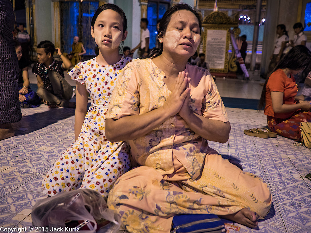 28 OCTOBER 2015 - YANGON, MYANMAR:  A woman and her daughter pray during observances of Thadingyut at Botataung Pagoda in Yangon. Botataung Pagoda was first built by the Mon, a Burmese ethnic minority, around the same time as was Shwedagon Pagoda, over 2500 years ago. The Thadingyut Festival, the Lighting Festival of Myanmar, is held on the full moon day of the Burmese Lunar month of Thadingyut. As a custom, it is held at the end of the Buddhist lent (Vassa). The Thadingyut festival is the celebration to welcome the Buddha's descent from heaven.   PHOTO BY JACK KURTZ
