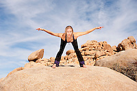 Woman in yoga pose bowing with hands in meditation mudra outdoors. Elise Kost jewelry.