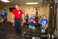 Laconia Fire's Ray Bushey with a crew of 4th graders helping him clean up with work out room during Granite United Way's Day of Caring joined by 300 Pleasant Street School students.  (Karen Bobotas/for the Laconia Daily Sun)