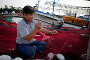 Korean fishermen workers repairing fishing net in Pohang harbor / South Korea, Republic of Korea, KOR, 04 October 2009.