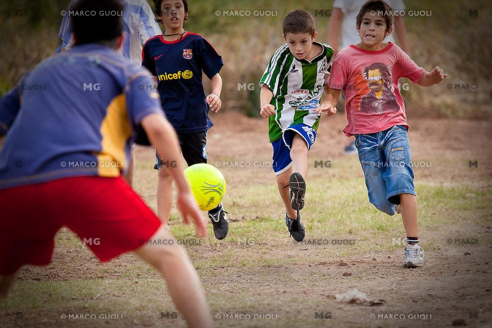 NINIOS JUGANDO AL FUTBOL AL AIRE LIBRE DURANTE UNA CLASE DE APOYO ESCOLAR DULCE ESPERANZA, DIQUE LUJAN, PROVINCIA DE BUENOS AIRES, ARGENTINA (PHOTO © MARCO GUOLI - ALL RIGHTS RESERVED)