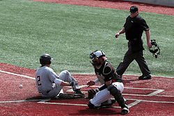 26 April 2014:  Tyler Rolland slides safely past Mike Hollenbeck to score as umpire Bret Bruington observes during an NCAA Division 1 Missouri Valley Conference (MVC) Baseball game between the Southern Illinois Salukis and the Illinois State Redbirds in Duffy Bass Field, Normal IL