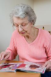 Older woman looking at a clothes catalogue,