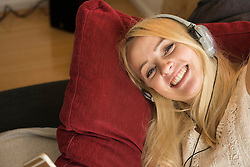 Portrait of a beautiful young woman listening to music and relaxing on sofa in the living room, Munich,Bavaria, Germany